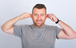 Young funny man holding his ears Stock Images