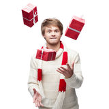 Young funny man juggle the christmas gifts Royalty Free Stock Photos