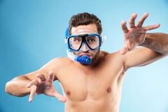 Young funny man playing with hands and wearing water mask Stock Photo