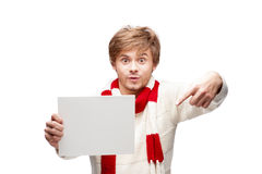 Young funny man pointing at sign. Portrait of young cheerful caucasian man which pointing at sign with funny expression Royalty Free Stock Image