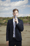 Young funny man with tie in mouth. Not serious business man on roof top Royalty Free Stock Photography