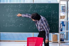 The young funny math teacher in front of chalkboard. Young funny math teacher in front of chalkboard stock photos