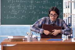 The young funny math teacher in front of chalkboard. Young funny math teacher in front of chalkboard royalty free stock photo