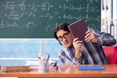 The young funny math teacher in front of chalkboard. Young funny math teacher in front of chalkboard royalty free stock images