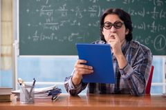 The young funny math teacher in front of chalkboard. Young funny math teacher in front of chalkboard royalty free stock photos