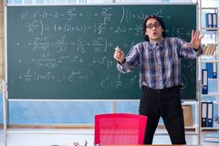 The young funny math teacher in front of chalkboard. Young funny math teacher in front of chalkboard stock images