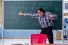 The young funny math teacher in front of chalkboard. Young funny math teacher in front of chalkboard royalty free stock image