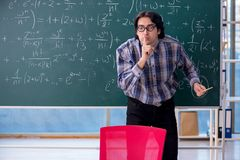Young funny math teacher in front of chalkboard. The young funny math teacher in front of chalkboard stock image