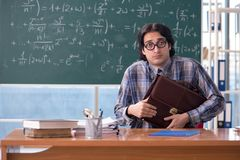 The young funny math teacher in front of chalkboard. Young funny math teacher in front of chalkboard stock photo