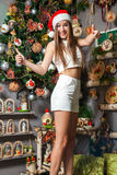 Young funny model with dark eyes, brown hair and santa hat celebrating new year at home Stock Image