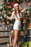 Young funny model with dark eyes, brown hair and santa hat celebrating new year at home. Young funny beautiful fashion model with dark eyes, brown hair and santa Stock Image