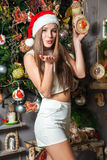 Young funny model with dark eyes, brown hair and santa hat celebrating new year at home Royalty Free Stock Images