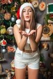 Young funny model with dark eyes, brown hair and santa hat celebrating new year at home. Young funny beautiful fashion model with dark eyes, brown hair and santa Stock Photo
