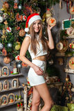 Young funny model with dark eyes, brown hair and santa hat celebrating new year at home. Young funny beautiful fashion model with dark eyes, brown hair and santa Stock Images