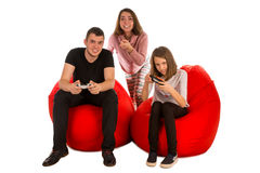 Young funny people are enthusiastic about playing video games while sitting on red beanbag chairs stock image