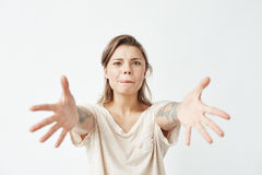 Young funny pretty girl stretching hands to camera over white background. Stock Photography