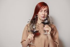 Young funny redhaired girl sommelier with fur cape on white background hold and smell two glasses red wine. Concept alcoholism, stock photos