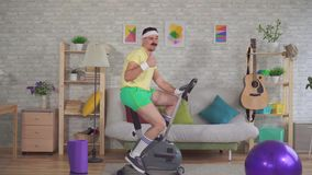 Young funny sportsman from the 80`s with a mustache is engaged on a exercise bike shows his thumb up stock video footage