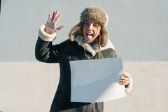 Young funny teen girl in winter clothes, hat showing clean white sheet of paper royalty free stock photography