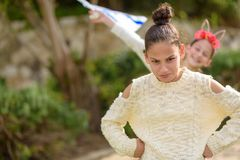 Young funny teenager girl standing outdoor with arms akimbo. Portrait of a young teen with hair bun standing with arms akimbo. Teenage girls friends having fun royalty free stock image