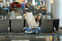 Young funny traveler tourist woman with crossed legs holding paper map, search route, waiting in lobby hall at. International airport. Passenger traveling stock photos