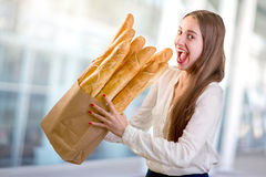 Young and funny woman eating baguettes in front of the bakery store Royalty Free Stock Images
