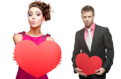 Young funny woman and handsome man holding red heart on white ba Royalty Free Stock Image