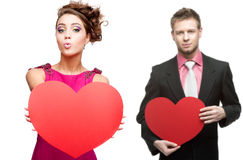 Young funny woman and handsome man holding red heart on white ba Royalty Free Stock Photography
