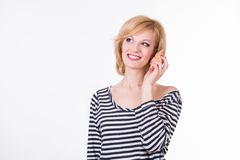 Young funny woman hearing sea shell and smiling Stock Photos