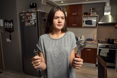 Young woman holding spanners, gender equality concept royalty free stock images