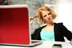 Young funny woman sitting at her workplace Stock Photos