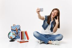 Young funny woman student doing take selfie shot on mobile phone show rock-n-roll sign blink near globe backpack school. Books isolated on white background stock photography