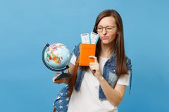 Young funny woman student in glasses with backpack holding world glove, passport, boarding pass tickets isolated on blue. Background. Education in university royalty free stock photography