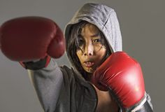 Young furious and angry Asian Chinese sporty woman in fitness top hoodie and boxing gloves training boxing workout throwing punch royalty free stock photography