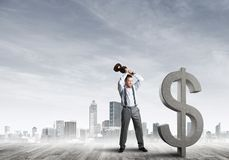 Determined banker man against modern cityscape breaking dollar concrete figure. Young furious businessman going to crash with violin stone dollar symbol stock photography