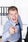 Young furious man is pointing with his finger in the office Royalty Free Stock Photos