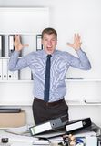 Young furious man is standing in front of many files Stock Images