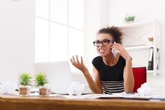 Business talk, furious woman talking on phone at office. Young furious woman talking on phone at modern office copy space. Business consulting Royalty Free Stock Images