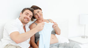 Young futur parents with chlidrens clothes Royalty Free Stock Images