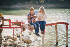 Young future parents and their dog in a funny costume sitting on a wooden bridge and having picnic near lake Royalty Free Stock Images