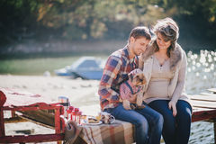 Young future parents and their dog in a funny costume sitting on a wooden bridge and having picnic near lake Royalty Free Stock Photography