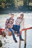Young future parents and their dog in a funny costume sitting on a wooden bridge and having picnic near lake Stock Photography