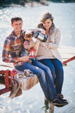 Young future parents and their dog in a funny costume sitting on a wooden bridge and having picnic near lake Royalty Free Stock Photo