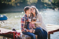 Young future parents and their dog in a funny costume sitting on a wooden bridge and having picnic near lake Stock Images