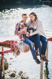 Young future parents and their dog in a funny costume sitting on a wooden bridge and having picnic near lake Royalty Free Stock Photos