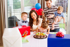 Young gal blowing out candles Royalty Free Stock Photos