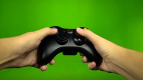 Game player hands controlling joystick keys playing on green screen