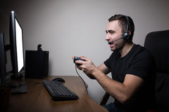 Young gamer in headphones and glasses using console and computer for playing game. In the night Royalty Free Stock Images