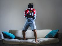 Young gamer man using VR goggles headgear and boxing gloves playing simulator 3D fight video game having fun on home sofa couch stock photos