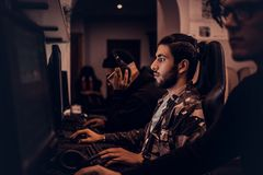 A young Indian gamer plays in a multiplayer video game on pc in a gaming club, enjoying spending time with her friends. royalty free stock photo